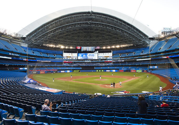 Photographers cover the game in an empty stadium during fourth-inning intrasquad baseball game action in Toronto, Friday, July 17, 2020. (Nathan Denette/The Canadian Press via AP)
