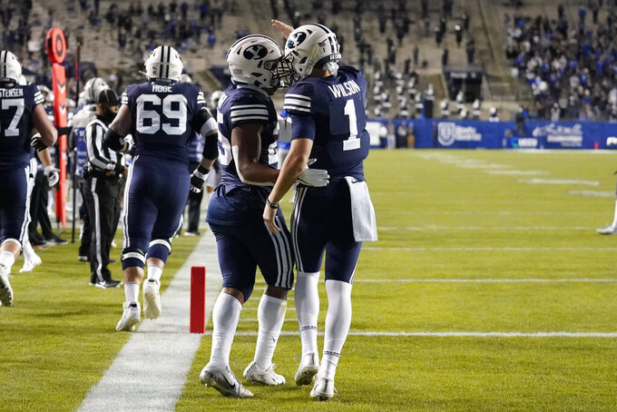 BYU quarterback Zach Wilson (1) celebrates with teammate Tyler Allgeier (25) after he scores against Texas State in the first half during an NCAA college football game Saturday, Oct. 24, 2020, in Provo, Utah. (AP Photo/Rick Bowmer)