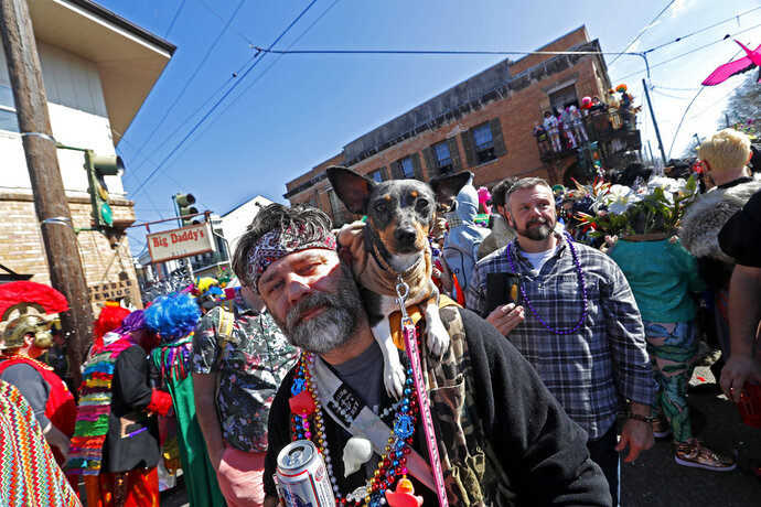 A man walks with his dog during the Society de Sainte Anne parade, on Mardi Gras day in New Orleans, Tuesday, Feb. 13, 2018. (AP Photo/Gerald Herbert)