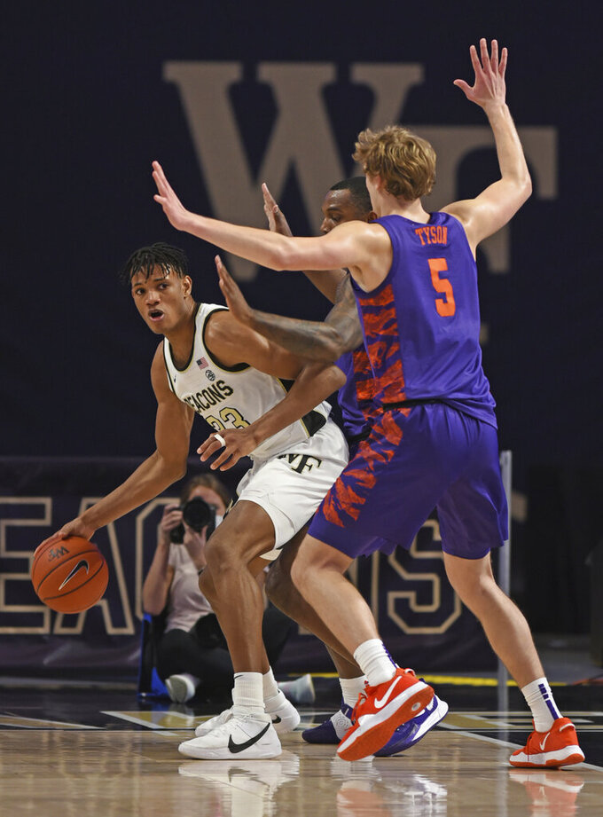 Wake Forest's Ody Oguama, left, looks for help as he is guarded by Clemson's Clyde Trapp and Hunter Tyson during the first half of an NCAA college basketball game, Wednesday, Feb. 24, 2021 at Joel Coliseum in Winston-Salem, N.C. (Walt Unks/The Winston-Salem Journal via AP, Pool)