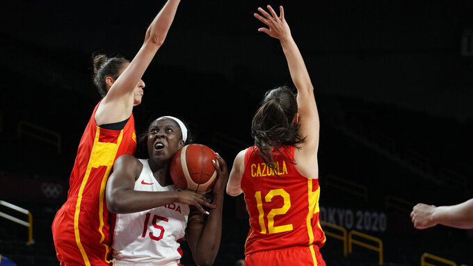 Canada's Laeticia Amihere (15) drives between Spain's Alba Torrens (7), left, and Maria Teresa Cazorla Medina (12) during women's basketball preliminary round game at the 2020 Summer Olympics, Sunday, Aug. 1, 2021, in Saitama, Japan. (AP Photo/Eric Gay)