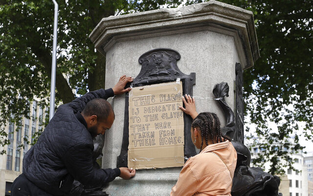 A banner is taped over the inscription on the pedestal of the toppled statue of Edward Colston in Bristol, England, Monday, June 8, 2020. The toppling of the statue was greeted with joyous scenes, recognition of the fact that he was a notorious slave trader — a badge of shame in what is one of Britain's most liberal cities. (AP Photo/Kirsty Wigglesworth)