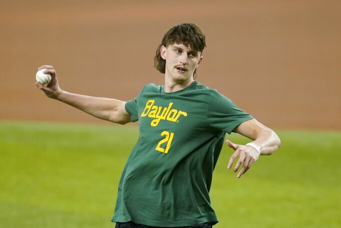 Baylor basketball player Matthew Mayer throws out a first pitch before a baseball game between the Seattle Mariners and the Texas Rangers in Arlington, Texas, Friday, July 30, 2021. (AP Photo/Tony Gutierrez)