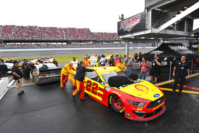 Joey Lagano's car is pushed out of pit row along with others after a NASCAR Cup series auto race was postponed until Monday due to rain, Sunday, Oct. 3, 2021, in Talladega, Ala. (AP Photo/John Amis)
