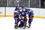 New York Islanders right wing Josh Bailey (12), left wing Anders Lee (27), and center Mathew Barzal (13) surround defenseman Ryan Pulock (6) after Pulock scored in overtime in the team's NHL hockey game against the Vegas Golden Knights, Thursday, Dec. 5, 2019, in Uniondale, N.Y. (AP Photo/Kathy Willens)