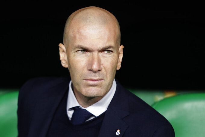 FILE - In this In this file photo dated March 8, 2020, Real Madrid's head coach Zinedine Zidane sits at the bench during La Liga soccer match in Seville, Spain. Zinedine Zidane is again stepping down as Real Madrid coach. The club says the Frenchman is leaving his job. It comes four days after a season in which Madrid failed to win a title for the first time in more than a decade. (AP Photo/Miguel Morenatti, File)
