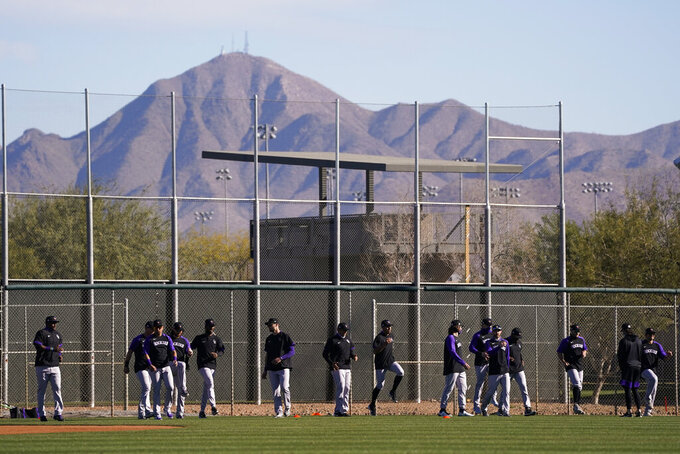 Colorado Rockies players warm up during the team's spring training baseball workout in Scottsdale, Ariz., Wednesday, Feb. 24, 2021. (AP Photo/Jae C. Hong)