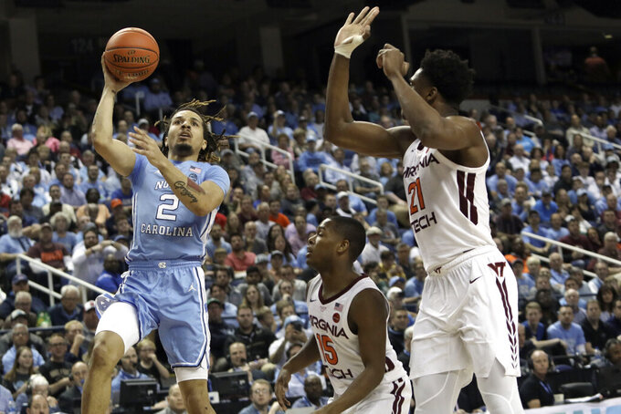 North Carolina guard Cole Anthony (2) looks to shoot while Virginia Tech guard Jalen Cone (15) and forward John Ojiako (21) defend during the first half of an NCAA college basketball game at the Atlantic Coast Conference tournament in Greensboro, N.C., Tuesday, March 10, 2020. (AP Photo/Ben McKeown)