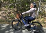 In this June 8, 2019 photo, Janice Goodwin rides her electric-assist bicycle on a paved road in Acadia National Park at Bar Harbor, Maine. E-bikes such as hers are allowed on paved roads but are banned on carriage paths and bicycle paths in the park. (AP Photo/David Sharp)