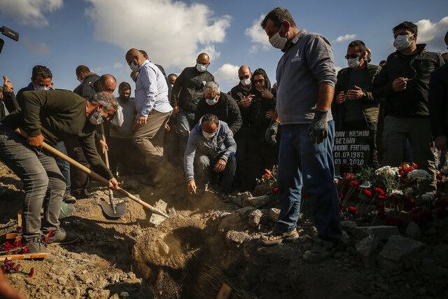 Mourner cover the grave of Fidan Gezgin, killed at her house when it collapsed during the Oct. 30 earthquake, during the funeral procession in Izmir, Turkey, Wednesday, Nov. 4, 2020. Fidan was the mother of Ayda Gezgin who was pulled alive from the rubble of the same building by rescue services Tuesday, some four days (91 hours) after the strong earthquake hit Turkey and Greece. (AP Photo/Emrah Gurel)