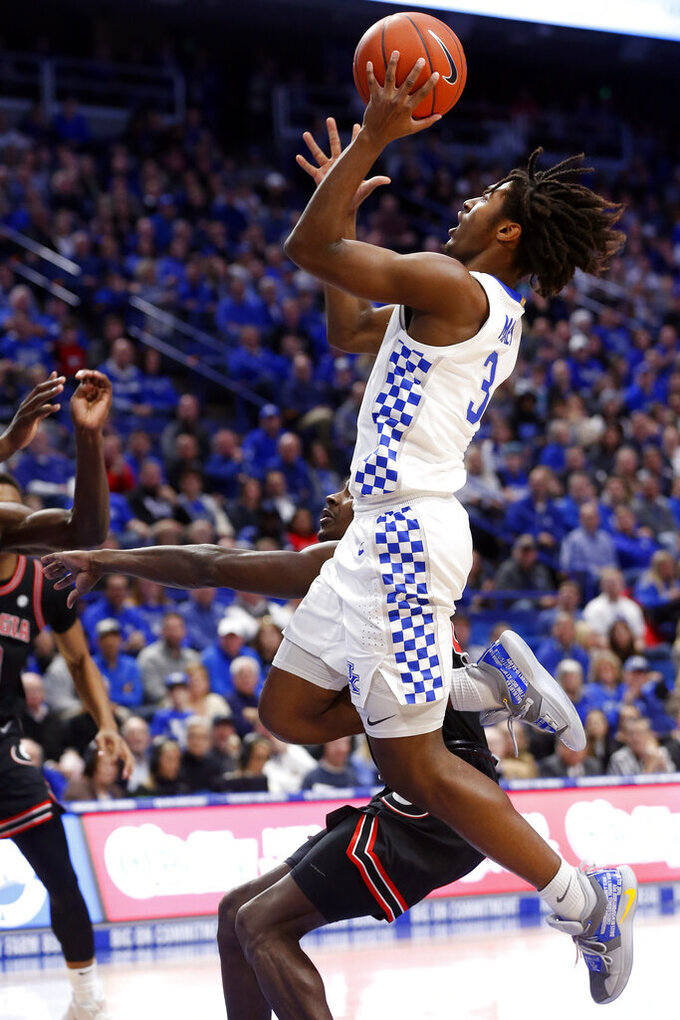 Kentucky's Tyrese Maxey (3) shoots near Georgia's Anthony Edwards during an NCAA college basketball game in Lexington, Ky., Tuesday, Jan 21, 2020. (AP Photo/James Crisp)