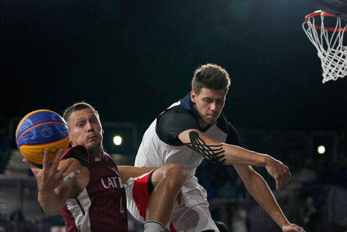 Kirill Pisklov, of the Russian Olympic Committee, right, and Latvia's Agnis Cavars reach for the ball during a men's 3-on-3 gold medal basketball game at the 2020 Summer Olympics, Wednesday, July 28, 2021, in Tokyo, Japan. (AP Photo/Jeff Roberson)