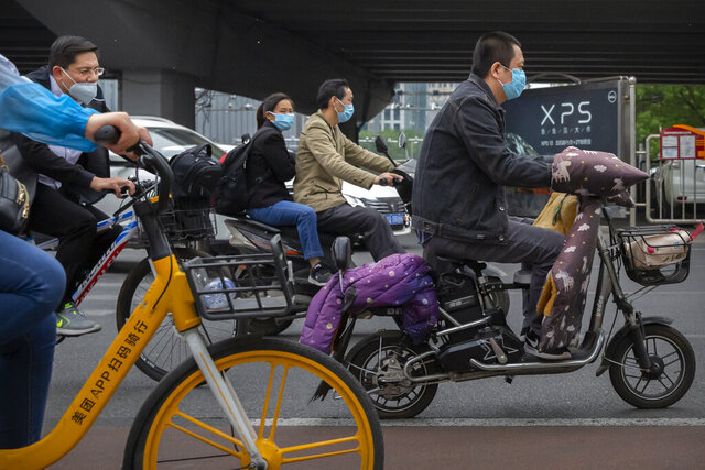 People pass by wearing face masks to protect against the spread of the new coronavirus as ride along a street in Beijing, Wednesday, May 6, 2020. China on Wednesday reported just two new cases of the coronavirus and no deaths. (AP Photo/Mark Schiefelbein)