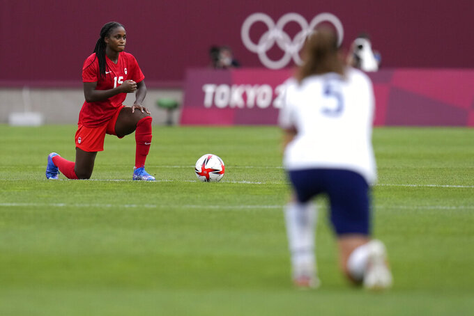 Canada's Nichelle Prince, left, kneels prior to a women's semifinal soccer match against United States at the 2020 Summer Olympics, Monday, Aug. 2, 2021, in Kashima, Japan. (AP Photo/Fernando Vergara)