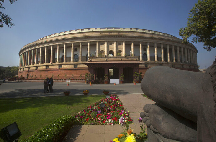 FILE- In this Feb. 23, 2016 file photo, the Indian parliament building is seen from behind a Mahatma Gandhi statue, right, in New Delhi, India. India's recent national election delivered a historic victory to Prime Minister Narendra Modi's Hindu nationalist party, but also exposed the influence of money, power and questionable morality on the world's largest democracy. (AP Photo/Manish Swarup, File)