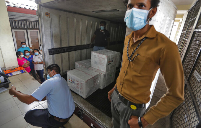 A Sri Lankan health services worker takes a selfie as others unload a consignment of Oxford-AstraZeneca vaccine donated by the Indian government at a medical warehouse next to a plain clothed police officer standing guard in Colombo, Sri Lanka, Thursday, Jan. 28, 2021. Sri Lanka's president on Thursday welcomed the first 500,000 doses of a COVID-19 vaccine from India, which has donated the shots to eight countries in the region. (AP Photo/Eranga Jayawardena)