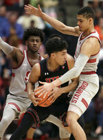 Utah guard Sedrick Barefield, center, looks to pass the ball as he is defended by Stanford guard Daejon Davis, left, and forward Jaiden Delaire during the first half of an NCAA college basketball game in Stanford, Calif., Thursday, Jan. 24, 2019. (AP Photo/Jeff Chiu)