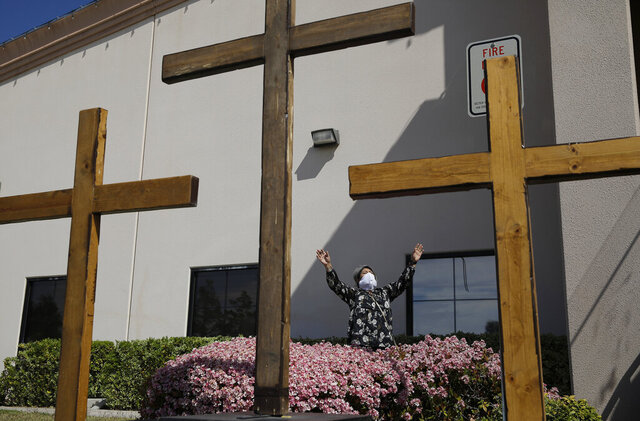FILE - In this April 12, 2020, file photo, a woman prays while wearing a face mask before speaking at an Easter drive-in service at the International Church of Las Vegas, in Las Vegas. Leaders of the rural Calvary Chapel Dayton Valley in Lyon County, Nev., are pleading with a federal appeals court in to overturn the state's COVID-19 restrictions on religious gatherings that they say treat them more severely than casinos and other secular activities in violation of the U.S. Constitution. Calvary Chapel Dayton Valley wants the 9th U.S. Circuit Court of Appeals in San Francisco to temporarily invalidate Nevada's 50-person cap on church services while the court considers whether to strike it down permanently. (AP Photo/John Locher, File)