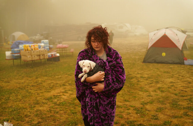Shayanne Summers holds her dog Toph while wrapped in a blanket after several days of staying in a tent at an evacuation center at the Milwaukie-Portland Elks Lodge, Sunday, Sept. 13, 2020, in Oak Grove, Ore.