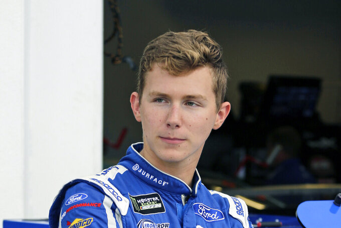 FILE - In this July 4, 2019, file photo, Matt Tifft stands outside his garage during a NASCAR auto race practice at Daytona International Speedway, in Daytona Beach, Fla. Tifft will miss the final three races of the NASCAR season after suffering a seizure at Martinsville Speedway. Tifft was at Martinsville preparing for the Saturday, Oct. 26, 2019, rookie meeting when he fell ill. He said in a social media post that tests Monday showed a brain tumor he had removed three years ago has not returned.(AP Photo/Terry Renna, File)