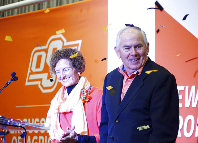 In this Wednesday, Jan. 15, 2020 photo, Kayleen and Larry Ferguson, who donated $50 million to Oklahoma State University, smile during the announcement in Stillwater, Oak.. Half of the donation will create an endowment for OSU agriculture students, and the other half will go toward the building of a new facility for agriculture research and learning at OSU. In recognition of the gift, the College of Agricultural Sciences and Natural Resources will be renamed the Ferguson College of Agriculture. (Tanner Holubar/The News Press via AP)