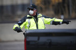 A Denver Police Department officer wears a surgical mask while directing traffic at a coronavirus drive-thru testing site outside the Denver Coliseum Saturday, March 14, 2020, in Denver. Officials planned to administer 150 tests but the line of vehicles wrapped around three city blocks. (AP Photo/David Zalubowski)