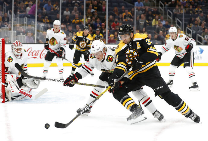 Boston Bruins' Patrice Bergeron tries to hold off Chicago Blackhawks' Adam Boqvist during the first period of an NHL preseason hockey game Saturday, Sept. 28, 2019, in Boston. (AP Photo/Winslow Townson)