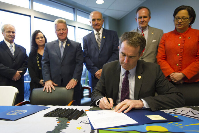 In this Feb. 16, 2018 photo provided by the Office of the Governor of Virginia, Virginia Gov. Ralph Northam signs Senate Bill 866 into law at Pioneer Community Hospital in Stuart, Va. About two years ago, the rural, mountainous Virginia county lost its only hospital, and local officials have now all but given up trying to bring it back. Northam signed bipartisan emergency legislation intended to help the Pioneer Community Hospital reopen. But in recent interviews, community leaders say they have moved on to seeking other ways to improve health care services in a county that sorely needs it. (Office of the Governor of Virginia)