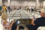 Collectors of vintage beer cans sit at their table on Thursday, Aug. 29, 2019, in Albuquerque, N.M., at the 49th annual gathering of members of the Brewery Collectibles Club of America. Collectors from around the world began Thursday buying, trading and selling containers of brews at the annual four-day event billed the