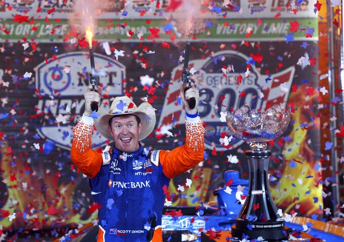 Scott Dixon fires a pair of six-shooters after winning the IndyCar Series auto race at Texas Motor Speedway on Saturday, May 1, 2021, in Fort Worth, Texas. (AP Photo/Richard W. Rodriguez)