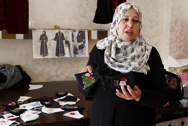 Suhad Saidam, shows stitched images of Santa Claus and Christmas on face masks at her sewing workshop in Gaza City, Monday, Dec. 14, 2020. In the blockaded Gaza Strip, the Christmas season is giving a boost to Saidam's business that produces pandemic face masks decorated with holiday symbols. They also have provided a small boost several dozen families in a Palestinian enclave run by the Islamic militant Hamas group. (AP Photo/Adel Hana)