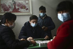 In this Jan. 25, 2020 photo, family members wear masks as they play mahjongg during a Lunar New Year gather in a village in Jianli County in central China's Hubei Province. As global anxiety about a new virus rises, Chinese authorities are striving to keep 50 million people in cities at the center of the outbreak both isolated and fed in the biggest anti-disease effort ever attempted. (Chinatopix via AP)