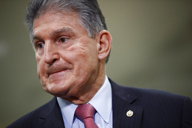 FILE - In this Feb. 5, 2020, file photo, Sen. Joe Manchin, D-W.Va., speaks with reporters on Capitol Hill in Washington. A bipartisan group of lawmakers, including Manchin,  is putting pressure on congressional leaders to accept a split-the-difference solution to the months-long impasse on COVID-19 relief in a last-gasp effort to ship overdue help to a hurting nation before Congress adjourns for the holidays. (AP Photo/Patrick Semansky, File)