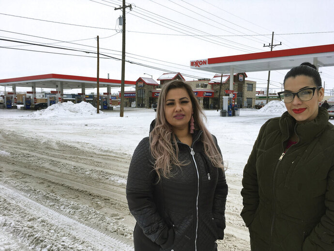 In this Wednesday, Jan. 23, 2019, photo provided by the ACLU of Montana, Martha Hernandez, left, and Ana Suda pose in front of a convenience store in Havre, Mont., where they say they were detained by a U.S Border Patrol agent for speaking Spanish last year. The women have filed a lawsuit against the U.S. government and the border agent and are seeking a judge's order barring U.S. Customs and Border Protection officials from stopping or detaining people based on race, accent or language. (Brooke Swaney/ACLU of Montana via AP)