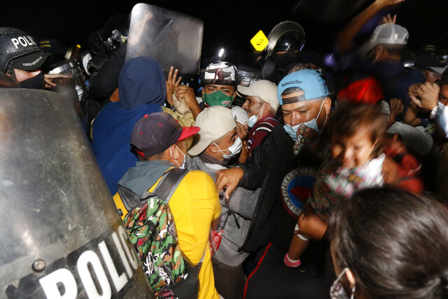 Honduran security forces try to keep migrants who are trying to reach the U.S. from crossing into Guatemala at the border in El Florido, Honduras, Friday, Jan. 15, 2021. (AP Photo/Delmer Martinez)