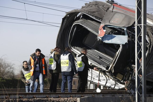 Police inspect an overturned carriage of a high-speed train after the train derailed in the countryside near the town of Lodi, northern Italy, Thursday, Feb. 6, 2020. A high-speed passenger train derailed in northern Italy before dawn on Thursday on the heavily used Milan-Bologna line, with the motor car completely detaching, killing two railway workers and injuring 27 people, authorities said. (AP Photo/Luca Bruno)
