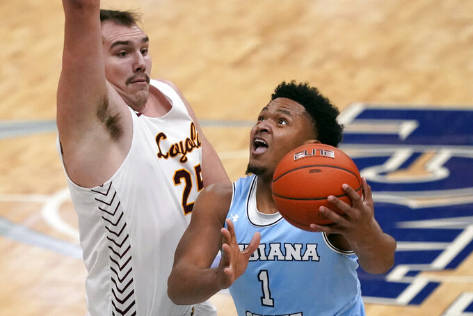 Indiana State's Tre Williams, right, heads to the basket as Loyola of Chicago's Cameron Krutwig (25) defends during the first half of an NCAA college basketball game in the semifinal round of the Missouri Valley Conference men's tournament Saturday, March 6, 2021, in St. Louis. (AP Photo/Jeff Roberson)