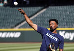 Seattle Mariners center fielder Dee Gordon tosses a ball before the team's baseball game against the Texas Rangers on Tuesday, May 15, 2018, in Seattle. Gordon could fill in at second base while Robinson Cano is out for 80 games on suspension for violating baseball's joint drug agreement. (AP Photo/Elaine Thompson)