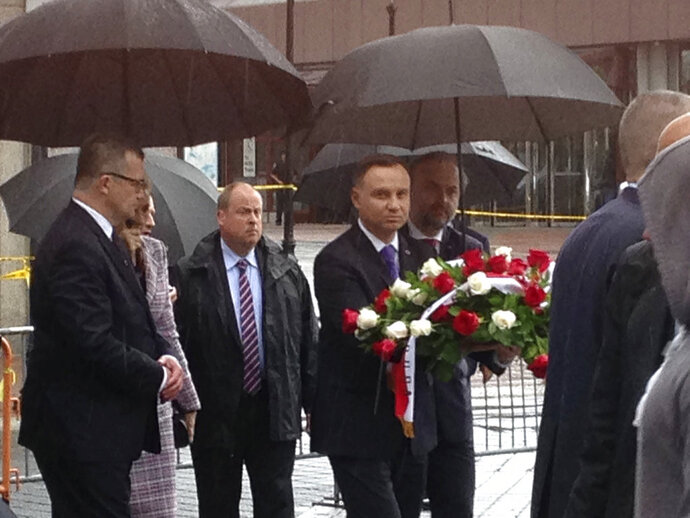 The president of Poland, Andrzej Duda, center, carries a bouquet of roses toward the waterfront statue commemorating the 1940 Soviet massacre of Poles, Wednesday, May 16, 2018. The bronze statue depicting a Polish soldier gagged, bound and impaled in the back with a bayonet in the 1940 Soviet massacre will be moved to a new location on the Hudson River, sparing it from storage and an uncertain fate. The statue was originally supposed to be placed in storage but that decision drew the ire of local Polish-American groups. (AP Photo/David Porter)