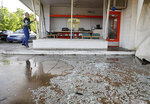 Tim Perdue starts to clean up his business,  A1 Auto Repair, after a suspected tornado which hit Sapulpa, Okla., early Sunday, May 26, 2019. (Mike Simons/Tulsa World via AP)