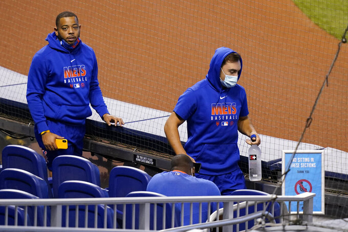 New York Mets players walks to the dugout before a baseball game against the Miami Marlins, Thursday, Aug. 20, 2020, in Miami. Major League Baseball says the Mets have received two positive tests for COVID-19 in their organization, prompting the postponement of two games. (AP Photo/Lynne Sladky)