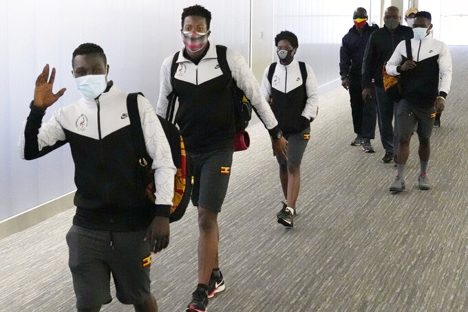 Members of Uganda's Olympic team arrive at Narita Airport in Narita, near Tokyo Saturday, June 19, 2021. A member of the team has tested positive for the coronavirus and was barred entry into Japan, in the first detected infection among arriving athletes for the Tokyo Games opening in five weeks. (Sadayuki Goto/Kyodo News via AP)