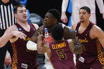 Illinois center Kofi Cockburn (21) is defended by Loyola Chicago center Cameron Krutwig, left, Keith Clemons (5) and Lucas Williamson (1) during the second half of a men's college basketball game in the second round of the NCAA tournament at Bankers Life Fieldhouse in Indianapolis, Sunday, March 21, 2021. (AP Photo/Paul Sancya)