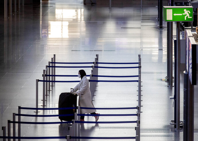 A woman walks through a terminal at the airport in Frankfurt, Germany, Thursday, March 26, 2020. For most people, the new coronavirus causes only mild or moderate symptoms, such as fever and cough. For some, especially older adults and people with existing health problems, it can cause more severe illness, including pneumonia. (AP Photo/Michael Probst)