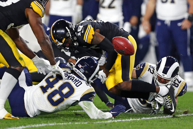 Pittsburgh Steelers wide receiver Diontae Johnson (18) fumbles the football as he is tackled by Los Angeles Rams linebacker Travin Howard (48) during the first half of an NFL football game in Pittsburgh, Sunday, Nov. 10, 2019. The Steelers recovered the fumble. (AP Photo/Keith Srakocic)