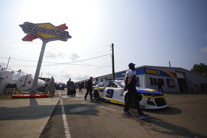 Pit crew members move Chase Elliott's car in the garage area before a NASCAR Cup Series auto race in Watkins Glen, N.Y., on Sunday, Aug. 8, 2021. (AP Photo/Joshua Bessex)