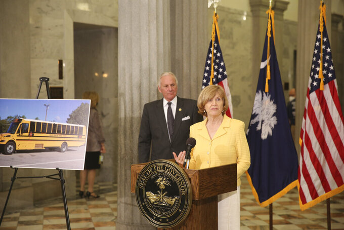 South Carolina Education Superintendent Molly Spearman, right, and Gov. Henry McMaster, left, announce the state will spend $24 million in a legal settlement on both school buses and regular buses that don't run on diesel fuel during a news conference on Tuesday, April 13, 2021, in Columbia, S.C. The money came from a settlement with Volkswagen over emission testing. (AP Photo/Jeffrey Collins).