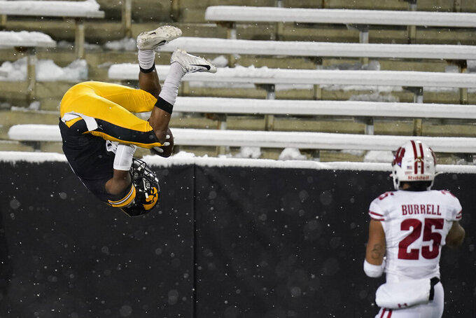 Iowa wide receiver Ihmir Smith-Marsette, left, flips in the end zone in front of Wisconsin safety Eric Burrell, right, after catching a 53-yard touchdown pass during the second half of an NCAA college football game, Saturday, Dec. 12, 2020, in Iowa City, Iowa. Iowa won 28-7. (AP Photo/Charlie Neibergall)