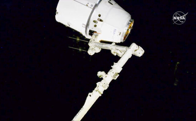 In this image taken from NASA video, NASA astronauts Andrew Morgan and Jessica Meir use the International Space Station's robot arm to capture the Dragon capsule Monday, March 9, 2020. The Dragon capsule reached the orbiting lab on Monday after launching from Cape Canaveral, Florida, late Friday night. It is SpaceX's 20th shipment to the space station.   (NASA via AP)