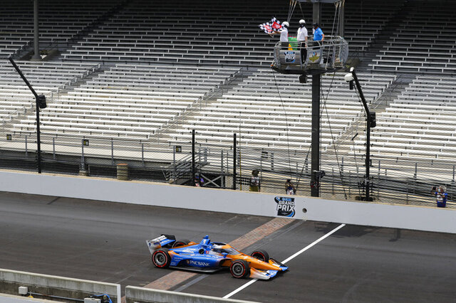 FILE - In this Saturday, July 4, 2020, file photo, race driver Scott Dixon, of New Zealand, takes the checkered flag as he crosses the start/finish line to win the IndyCar auto race at Indianapolis Motor Speedway in Indianapolis. The IndyCar series will welcome fans for the first time of the year during the REV Group Grand Prix doubleheader Saturday and Sunday, July 11-12, at Road America in Plymouth, Wisconsin. (AP Photo/Darron Cummings, File)